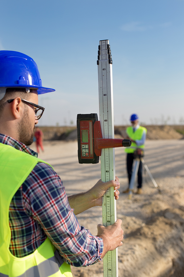 Construction Worker Holding Laser Measuring Tool On Building Sit